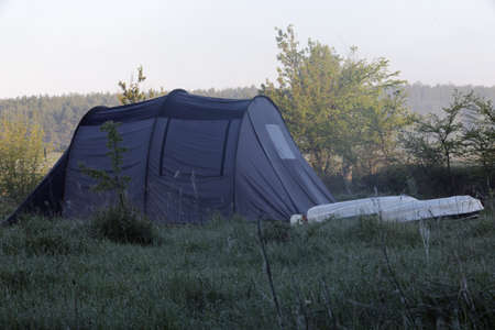 upturned: Tent and two upturned kayaks in the morning meadow at soring