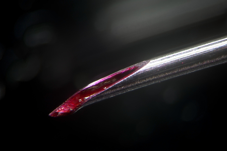 Dirty medical needle tip. Blood in canal not sterile used syringe. Unsanitary injections and infection risk. Morphinism drug addiction. Super macro close-up by microscope Stock Photo