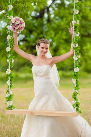 Bride on swing on green glade photo