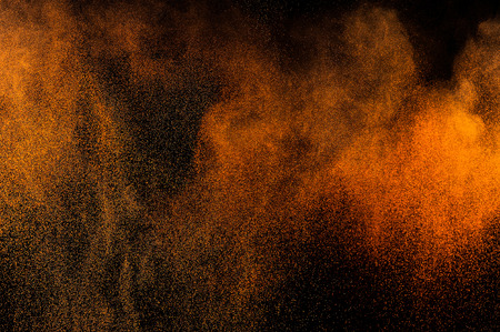Abstract orange paint Holi. Abstract orange powder explosion on black background.