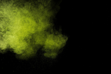 green powder: Abstract green powder explosion on black background.