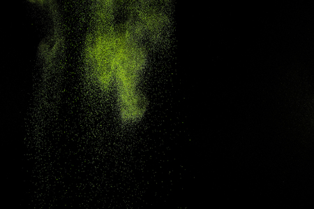 green powder: Abstract green paint Holi. Abstract green powder explosion  on black background.