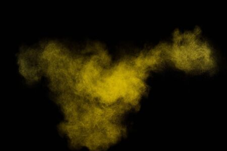 colored powder: Yellow powder explosion on black background. Colored powder cloud. Colorful dust explode. Paint  Holi. Stock Photo