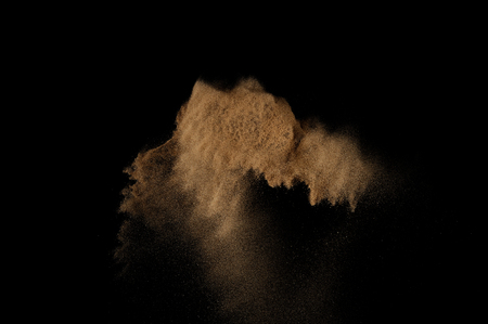 sandy soil: Sandy explosion isolated on black background. Abstract sand cloud.