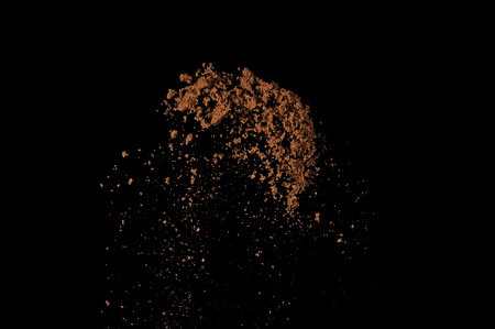 throw up: Soil explosion isolated on black background. Abstract cloud of brown ground.