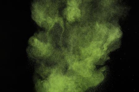 citron: Light green powder explosion on black background. Citron color cloud. Lime dust explode. Freeze motion paint  Holi.