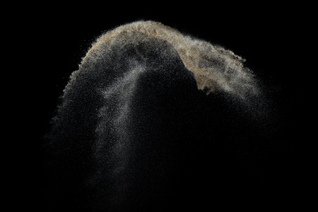 Sandy explosion isolated on black background. Abstract particles cloud. Texture element for design. Stock Photo