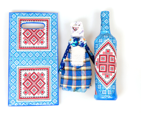 decoupage: Doll motanka, glass bottle and wooden board decorated with decoupage in Ukrainian style Stock Photo