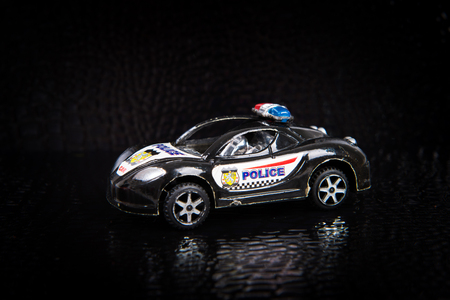 patrol: Toy police car on a black background, street patrol, criminal delay included flashing lights, protection order in accordance with the law Stock Photo