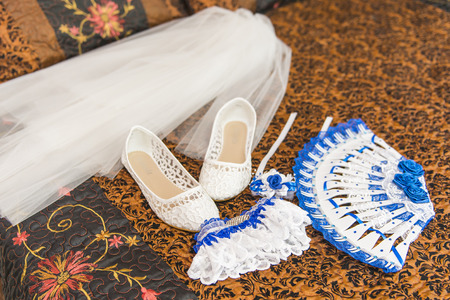 dowry: Wedding accessories for the morning of the bride in white blue . Wedding bouquet and shoes of the bride. Garter, shoes, fan, veil bride on the bed.