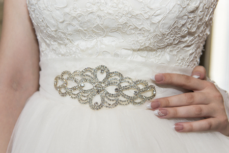 waist belt: Fragment of a wedding dress with a belt decorated with precious stones and pearls. Waist and hand on hip, the brides wedding dress is decorated with a brooch. Stock Photo