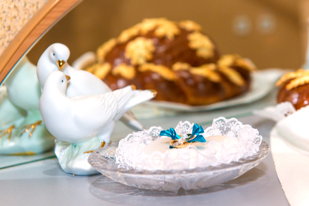 registrar: Gold wedding rings on a crystal plate in the registry office before the ceremony, family, wedding traditions and mural wedding in blue style, doves symbol of loyalty
