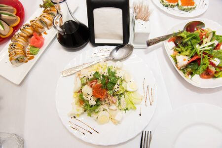 european cuisine: Salad with salmon, caviar, vegetables and quail eggs. Delicacy of European cuisine. Stock Photo