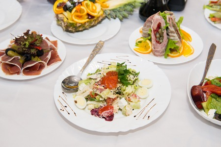 european cuisine: healthy food salad with vegetables and tuna fish. Salad with salmon, caviar, vegetables and quail eggs. Delicacy of European cuisine.