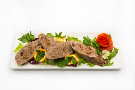 meatloaf: meatloaf stuffed with mushrooms. Meatloaf with mushrooms, garnished with lettuce, tomato, oranges. Delicacy from the chef Stock Photo