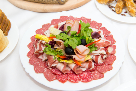 Plate of cold meats in the restaurant. Meat snacks. Smoked sausage and bacon, decorated with parsley and olives.