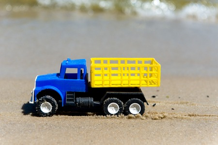 carretilla de mano: Toy cars on the wet sand. Summer vacation at sea.