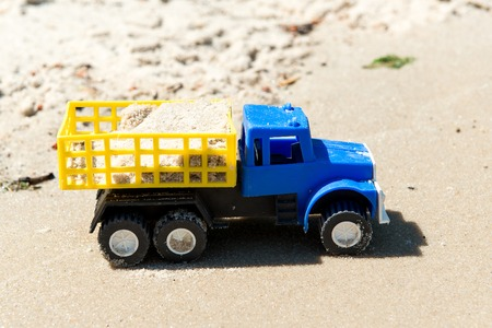 Toy cars on the wet sand. Summer vacation at sea.