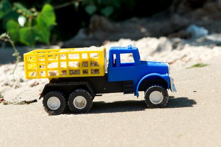 carretilla de mano: Coches de juguete en la arena mojada. Vacaciones de verano en el mar.