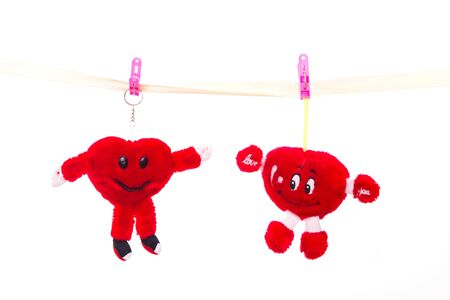 strapped: Soft toy strapped clothespins hanging heart on Valentines Day Stock Photo
