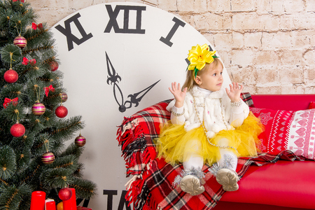 The child, a little girl sitting near a well-dressed Christmas tree and unwraps a gift.