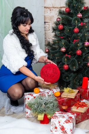 The girl, a cute brunette posing on the background of Christmas decorations.