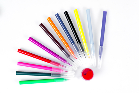Colored markers laid out near the jars with paints like solar rays. Stationery on white background.