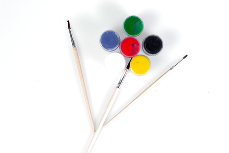 Jars with colored gouache and brush for drawing on a white background laid out in the shape of a flower. Stock Photo