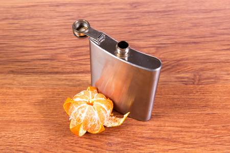 Steel flask with alcohol is on the table, along with a slice of tangerine. Alcohol addiction. Stock Photo
