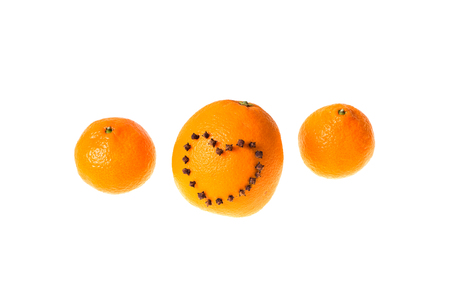 orange peel clove: Fresh juicy bright tangerine and orange decorated with a heart of carnation on a white background.