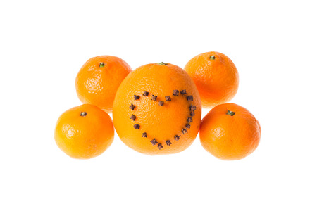 Fresh juicy bright tangerine and orange decorated with a heart of carnation on a white background.