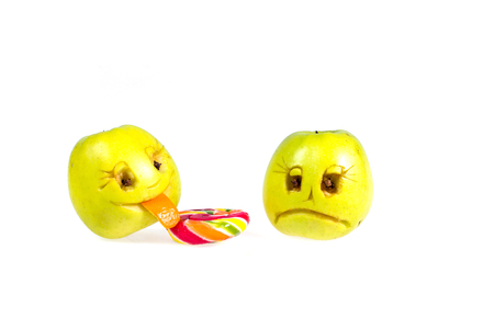 Happy and sad emoticons apple licking a lollipop. Feelings, attitudes and emotions. Stock Photo