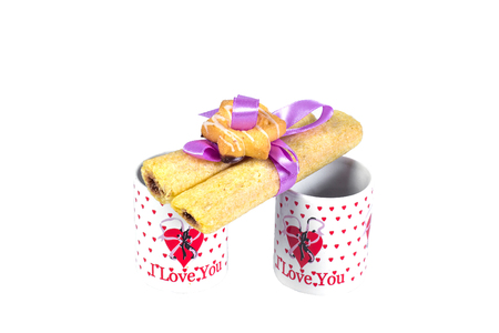 Two cups of coffee with a declaration of love and cookies tied with ribbon on a white background.
