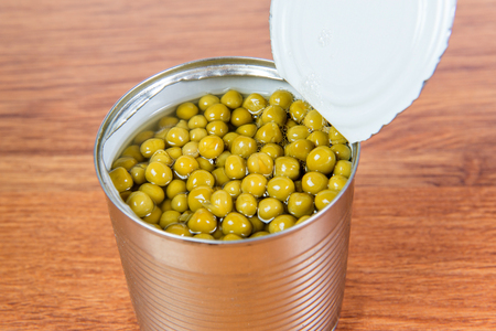 Green canned peas in open iron bank is on the table.