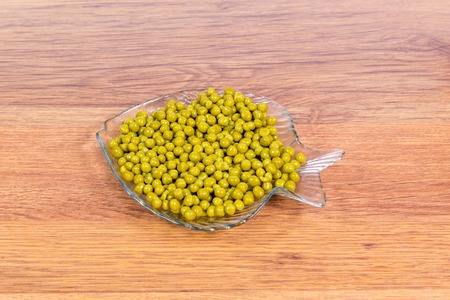 Canned green peas in a glass plate in the form of fish close-up on the table. Stock Photo