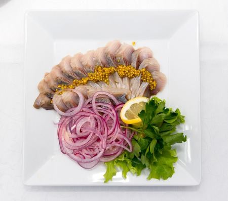 Sliced herring with purple onions, lemon and herbs flavored with mustard in beans.