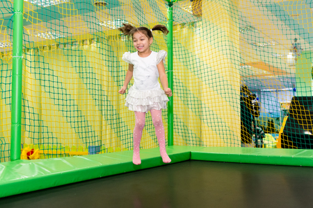 The girl in the birthday fun jumping on a trampoline. Joyful and carefree childhood.