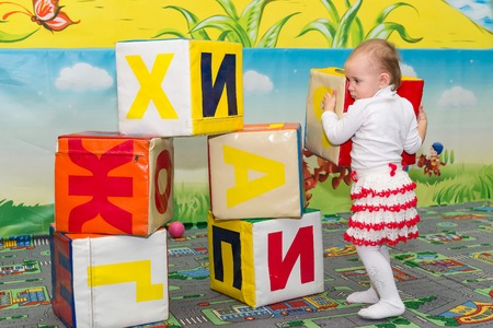 entertainment center: Little girl plays in the entertainment center with colored cubes which show the letters of the alphabet. Stock Photo