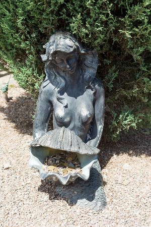 A statue of a fairy-tale character - a mermaid with a cockleshell in her hands decorates an alley in the park.