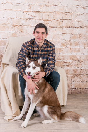 A man and a hussy dog are posing in the studio. The basics of training pets. Banco de Imagens