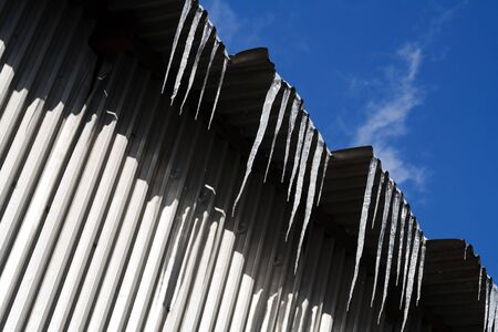 Icicles hanging from a roof in the sunshine Stock Photo - 651289