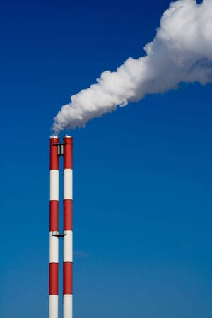 The chimney of a factory with white smoke. Vertical