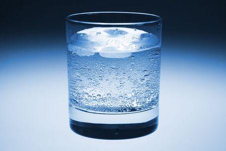 sorbo: Cristal fr�o de agua mineral chispeante con hielo. Con La Trayectoria Del Truncamiento Foto de archivo