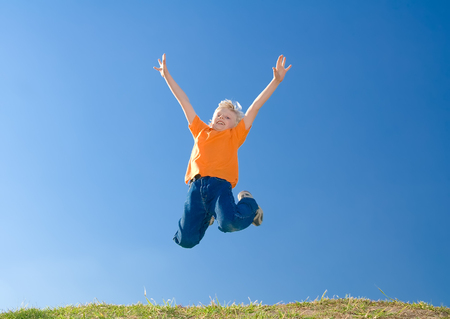 Jumping cute boy on a blue sky