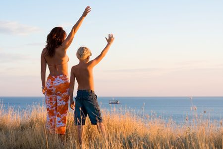 Happy mother and son wave hands at sunset Stock Photo - 1799791
