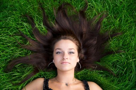 Young nice girl lying on the green grass with brown hair Stock Photo - 3711997