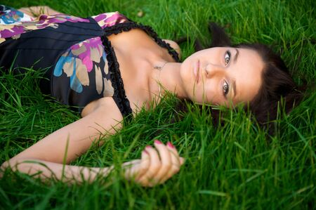 Young nice girl lying on the green grass with brown hair Stock Photo - 3711994