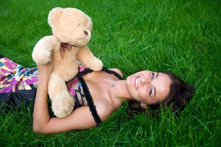 Young smile girl lying on the green grass with teddy bear Stock Photo - 3711996