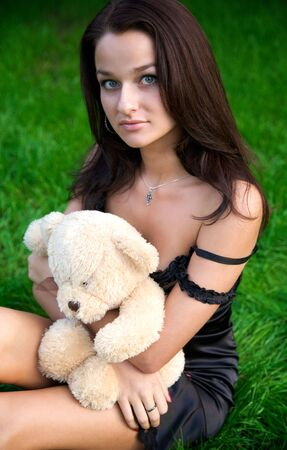 Young smile girl sitting on the green grass with teddy bear photo