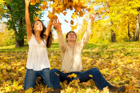 Young happy couple throwing autumn leaves in the air